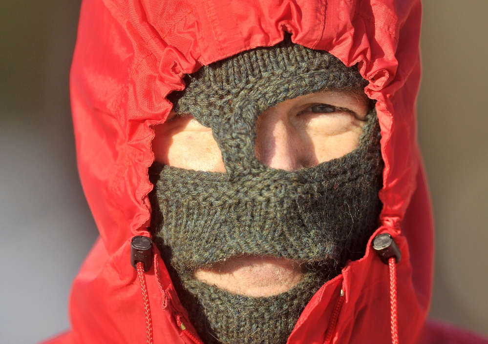 "COLD SNAP: Mark ""Dog"" Wallace covers up as much skin as he can for a walk on Quarry Road in Waterville on Friday. Temperatures hovering at or below 0 degrees and a winter storm are expected to grip central Maine over the weekend."