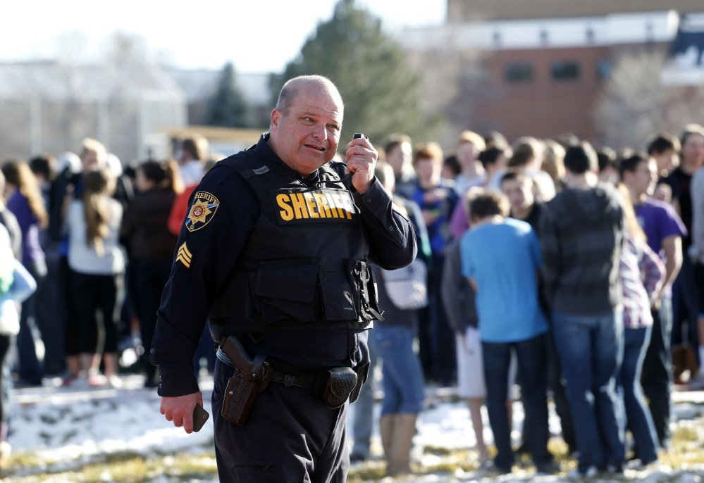 A sheriff deputy talks on his radio at Arapahoe High School in Centennial, Colo., on Friday. A student shot two other students before killing himself, authorities said.