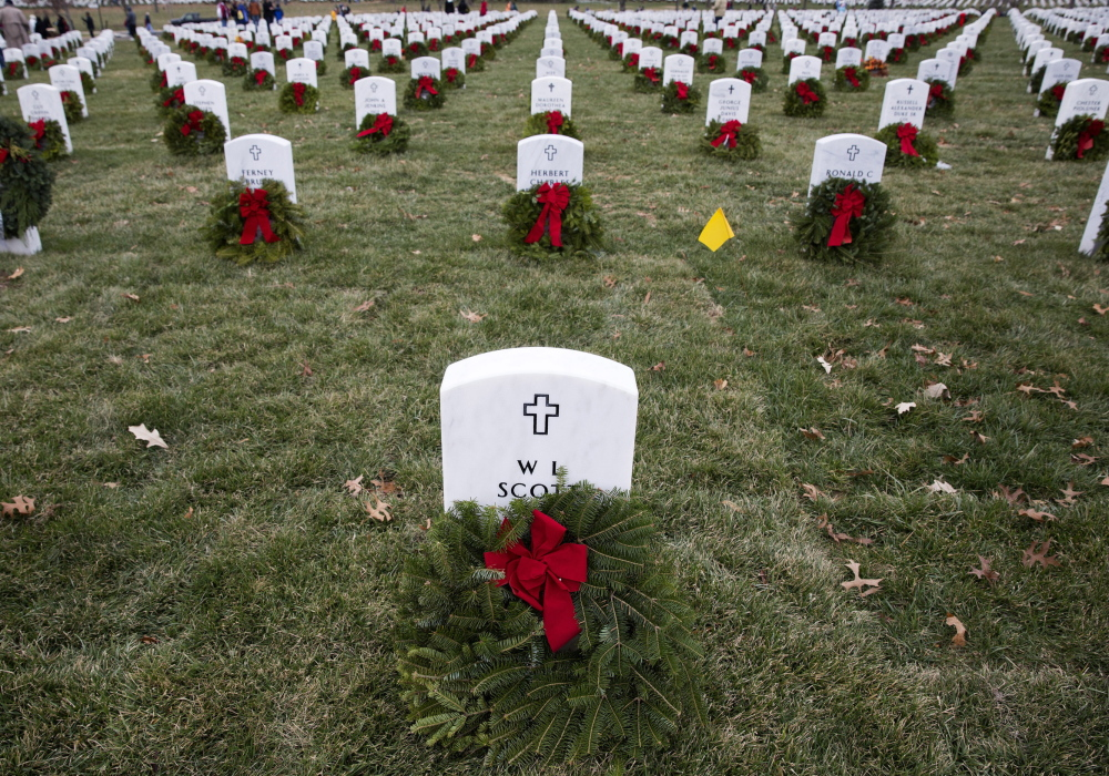 Remembrance wreaths from Maine rest in front of graves at Arlington National Cemetery in Washington on Saturday, National Wreaths Across America Day. Volunteers and families of the fallen placed thousands of the wreaths on headstones throughout the cemetery.