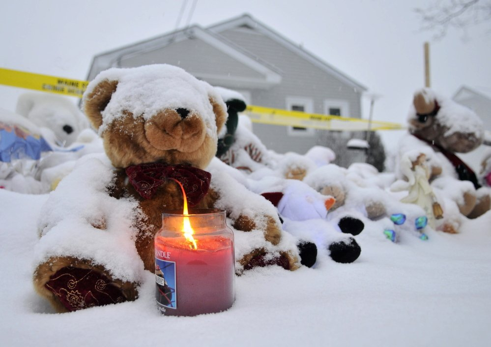 Staff photo by Michael G. Seamans A candle illuminates a growing teddy bear shrine for missing 20-month-old Ayla Reynolds outside her 29 Violette Ave residence in Waterville on Christmas Day.