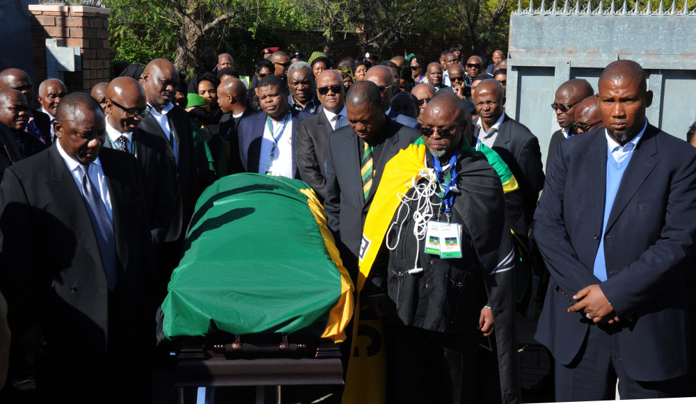 Nelson Mandela's grandson Mandla Mandela, right, and members of the African National Congress escort the casket of former South African President Nelson Mandela as it arrives at the Mandela residence in Qunu, South Africa on Saturday. Mandela will be put to rest after funeral services on Sunday.