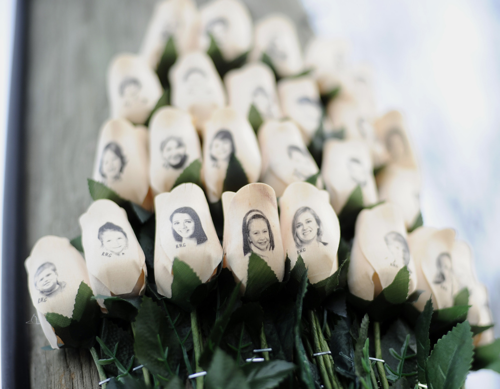 (File) White roses bearing the faces of victims of the Sandy Hook Elementary School shooting are displayed on a telephone pole near the school in Newtown, Conn. Adam Lanza opened fire inside the Sandy Hook Elementary School on Friday, Dec. 14, 2012, in Newtown, killing 26 students and educators.