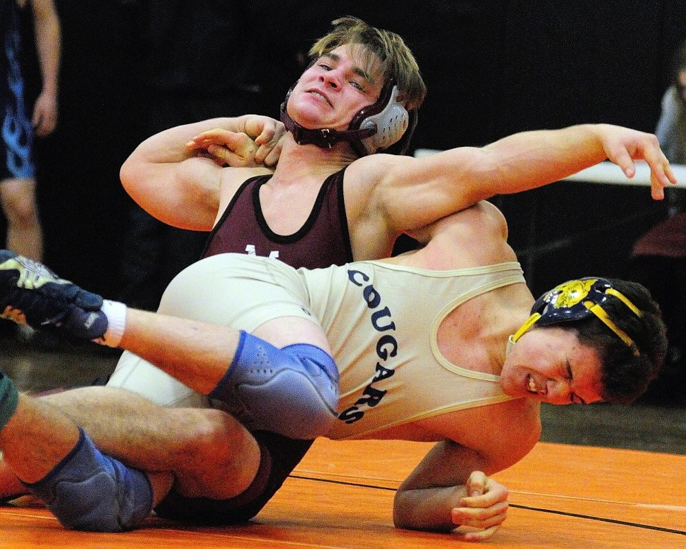 Monmouth Academy's James Gambino, top, and Mount Blue's Danny Reed compete in a 138-pound championship semi-finals during the Tiger Invitational on Saturday December 14, 2013 in the John A. Bragoli Memorial Gym in Gardiner.