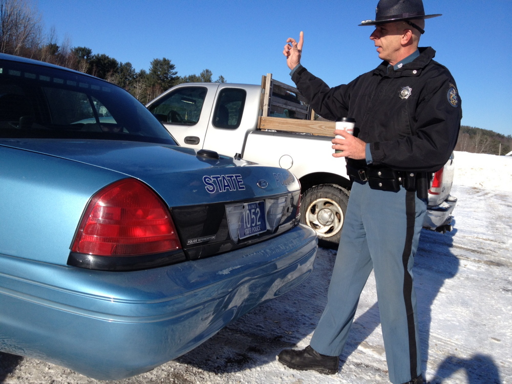 Trooper Sam Tlumac inspects his cruiser Monday morning after it was rear-ended on Route 202 in Manchester. Tlumac was assisting a motorist around 10 a.m. when a pickup struck the rear of his vehicle while it was parked on the side of the road. No injuries were reported. The state cruiser was a loaner after Tlumac's primary vehicle was destroyed when it was rear ended Dec. 1 in Pittsfield. State law requires motorists to move over one lane when passing troopers and other emergency vehicles parked on the side of the road.