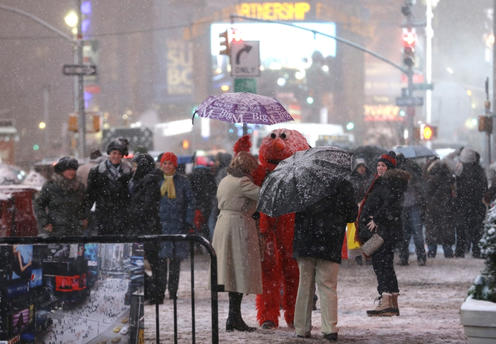 A person wearing an Elmo outfit holds an umbrella for a woman as she searches for money to give to the character after posing for a photo together at Times Square, Saturday, Dec. 14, 2013, in New York. Manhattan is experiencing heavy snow with reports saying the weather will continue to cover the city with snow throughout the night.