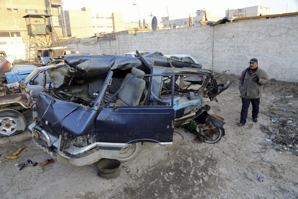 The Associated Press An Iraqi man inspects damaged vehicles in a car bomb attack in Baghdad, Iraq, Monday, Dec. 16, 2013. Iraqi officials say bombings in and around Baghdad have killed and wounded tens of people.