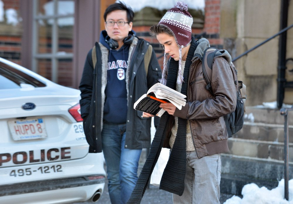 Students wait outside a building at Harvard University in Cambridge, Mass., Monday, Dec. 16, 2013. Four buildings on campus were evacuated Monday after campus police received an unconfirmed report that explosives may have been placed inside, interrupting final exams.