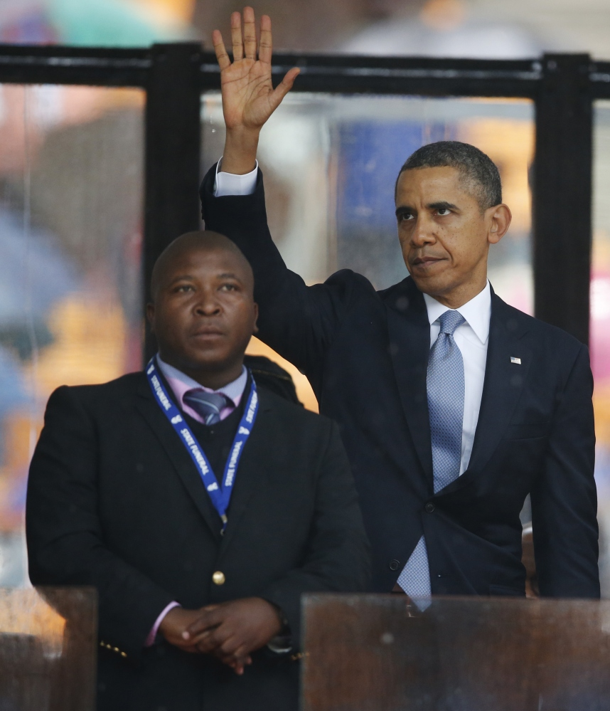 President Barack Obama waves standing next to the sign language interpreter after making his speech at the memorial service for former South African president Nelson Mandela at the FNB Stadium. South Africa's deaf federation said on Wednesday that the interpreter on stage for Mandela memorial was a 'fake'.