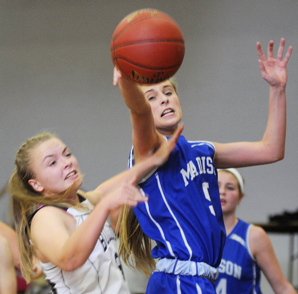 Staff photo by Andy Molloy Madison Area Memorial High School's Bronte Elias, right, grabs a rebound from Hall-Dale High Schools Eva Shepherd during a basketball match up Monday in Farmingdale.