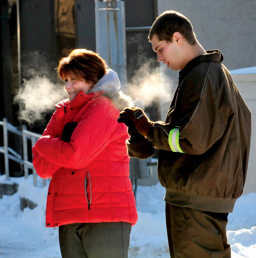 COLD RUSH: Warm breath turned to cold vapor as Laurie Laliberte and delivery driver Peter Schultz waited outside to receive packages from a United Parcel Service truck on a frigid day in Waterville on Tuesday.