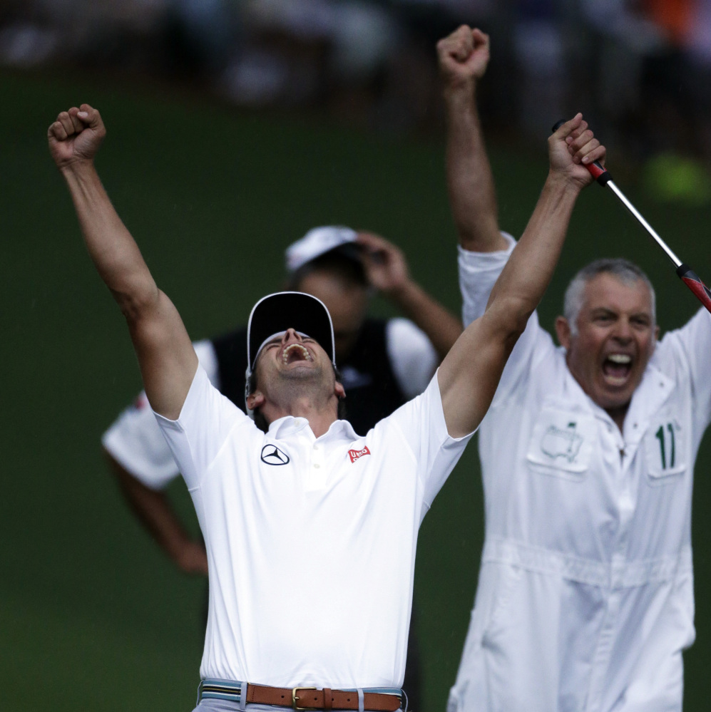 FILE - In this April 14, 2013 file photo, Adam Scott, of Australia, front, celebrates with caddie Steve Williams after making a birdie putt on the second playoff hole to win the Masters golf tournament in Augusta, Ga. Every major championship features a signature shot, some easier to define than others. And with every major champion, there is another shot that is equally pleasing to them even if hardly anyone else noticed. (AP Photo/Darron Cummings, File)