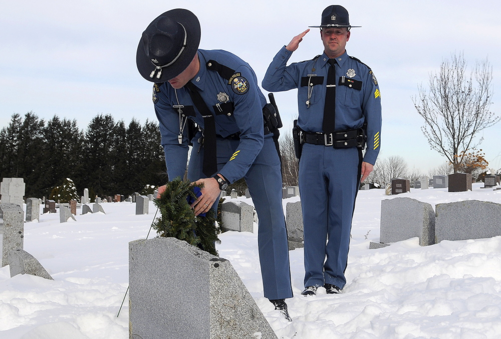 Maine State Police Sgt. Bruce Scott salutes as Trooper Elisha Fowlie lays a wreath Tuesday on the headstone of Trooper Michael Veilleux at St. Mary's Cemetery in Manchester. During a memorial service Tuesday, wreaths were placed on the headstones of 11 state police troopers who died in the line of duty. Organizers hope that the service will be an annual tradition, State Police Lt. Scott Ireland said. Retired troopers and friends of Veilleux remembered the 24-year-old who was killed in a car accident in Dayton in 1986.