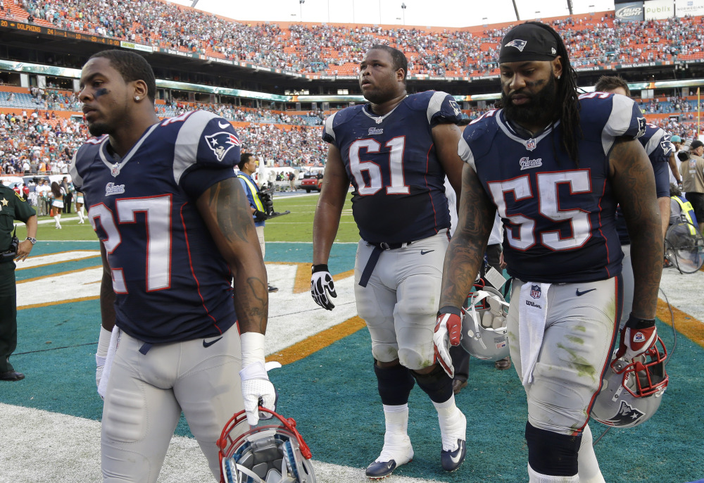 New England Patriots strong safety Tavon Wilson (27), tackle Marcus Cannon (61) and middle linebacker Brandon Spikes (55) walk off the field after they lost to the Miami Dolphins 24-20 in an NFL football game, Sunday, Dec. 15, 2013, in Miami Gardens, Fla. (AP Photo/Lynne Sladky)