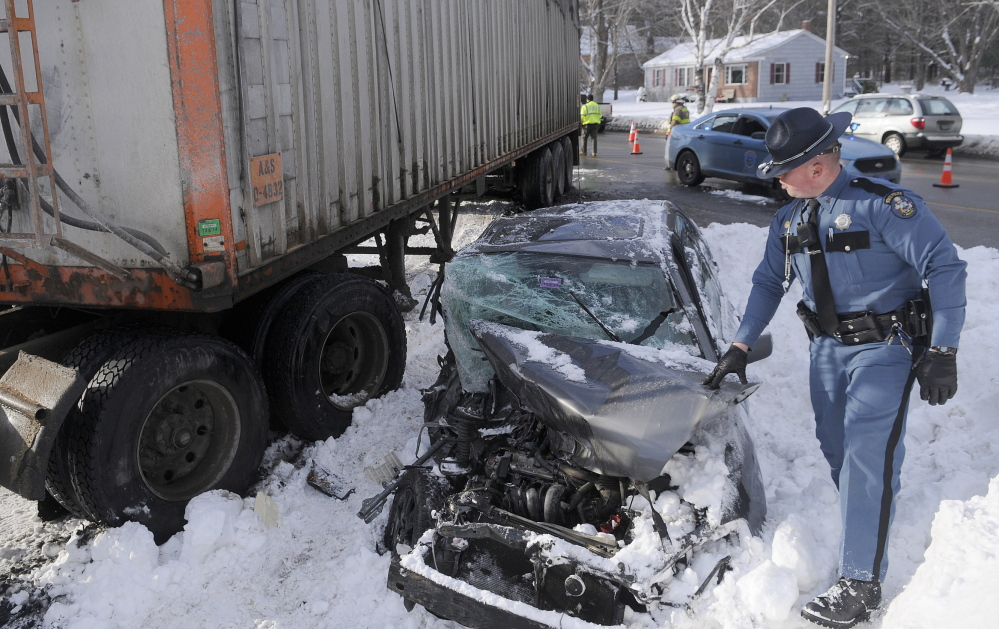 Serious crash: State Trooper Dane Wing walks around a car that was crushed beneath a tractor-trailer Wednesday afternoon on U.S. Route 202 in Manchester. The operator of the car was taken to the hospital.