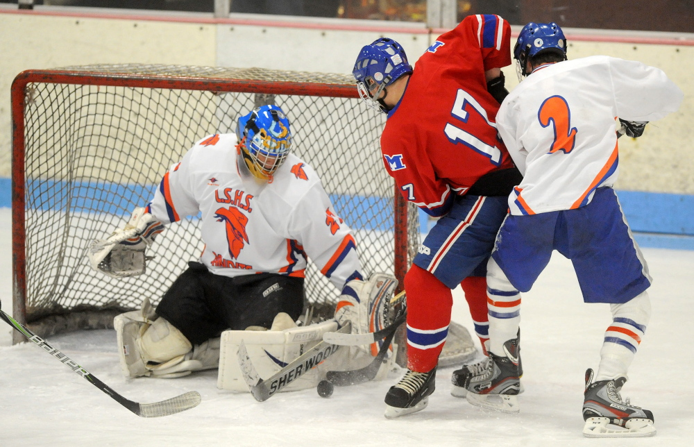 Lawrence/Skowegan goalie Sam Edmondson, 27, makes a save as Messalonskee High School's Dan Condon, 17, fights for the rebound with Lawrence/Skowhegan's Andrew Carpenter, 2, in the first period at Sukee Arena in Winslow on Wednesday.