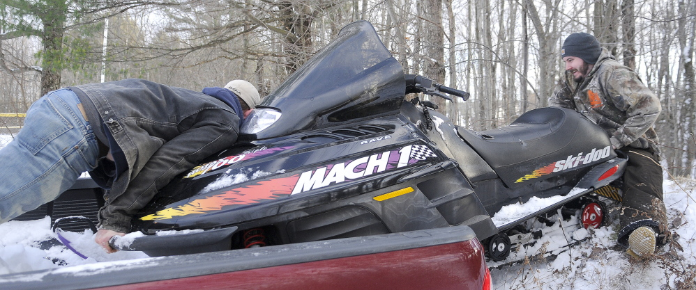 REVERSE: Josh Grant, left, pushes as Blake Cahill pulls a snowmobile off the bed of his pickup truck in Hallowell Wednesday. Cahill had just bought the machine and was taking it for an inaugural ride on the trails through the city.