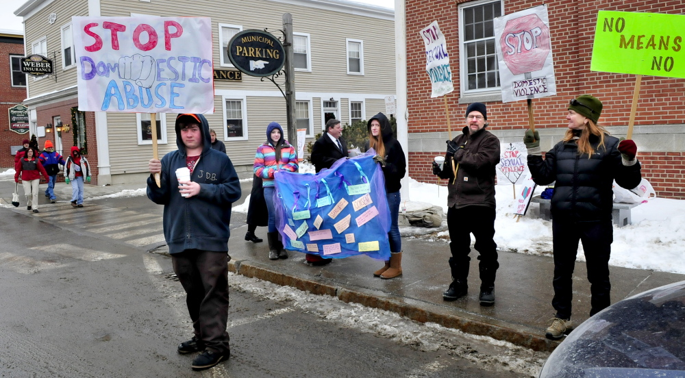 silent AND CLEAR: Mt. Blue High School students and staff demonstrate silently against sexual violence by holding signs and distributing information on Main Street in Farmington on Thursday. From left are Jonah Bragg, Cassie Ross, Tashia Berkey and teacher John Schoen and his wife, Patty.