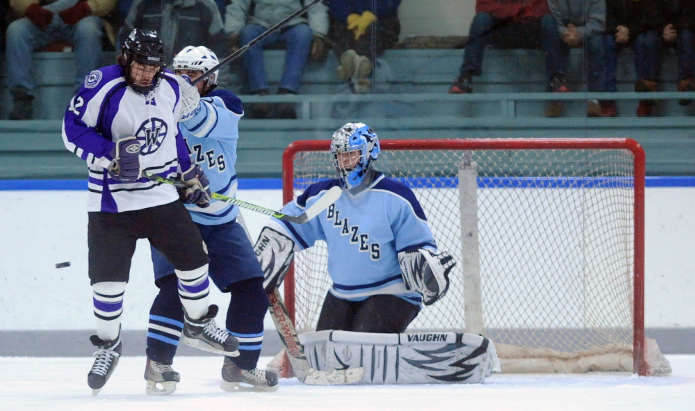 Waterville Senior High School's Thomas Samson, 12, jumps out of the way of the puck as Westbrook High School defender Darian Doucette, 24, tries to push him out of the way on the first period goal at Colby College on Thursday.