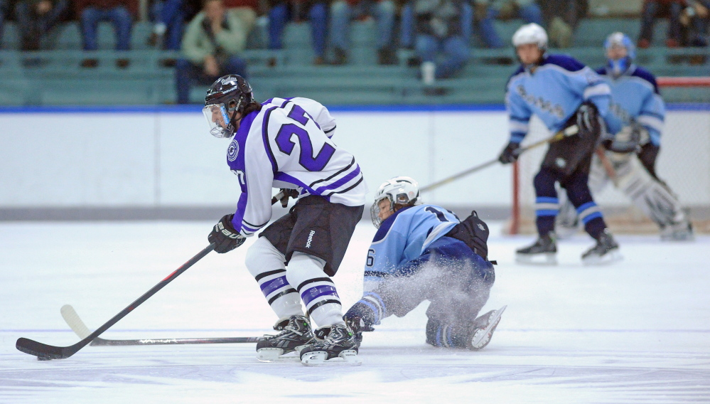 Waterville Senior High School's Christopher Lee, 27, skates after the puck as Westbrook High School's Dylan Francoeur, 16, in the first period at Colby College on Thursday.