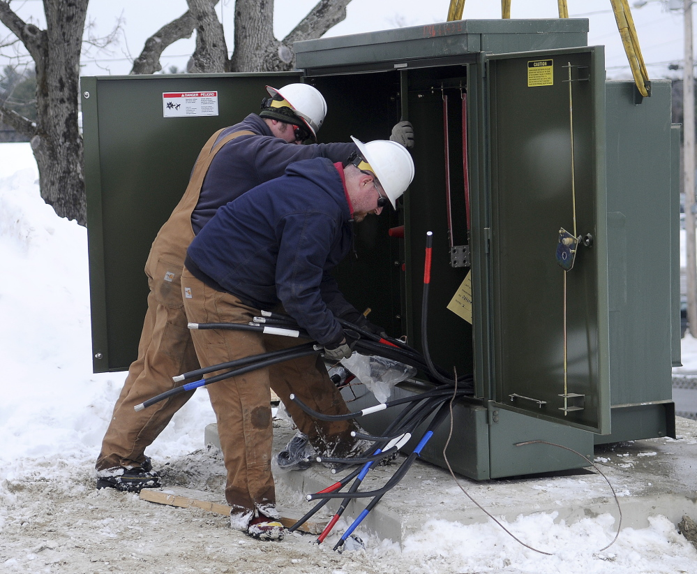 TURNED IT ON: Central Maine Power lineman Jason Hawes, right, and Garret Couturier install a power main Thursday in Augusta ahead of a potential ice storm forecast to arrive on Sunday.