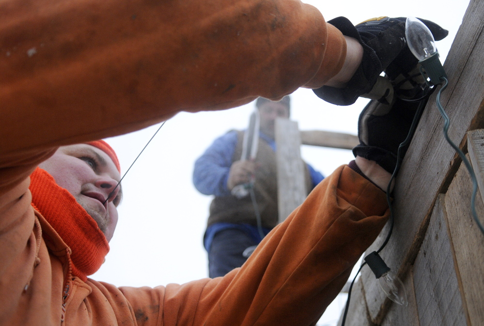 AWAY IN A MANGER: EJ Perry Construction employees Scott Gress, left, and John Kinnie set lights on a manger they built Friday on Water Street in Hallowell. The First Baptist Church of Hallowell will present a live nativity scene Christmas Eve at the creche, which was built with labor donated by Perry Construction of Hallowell.
