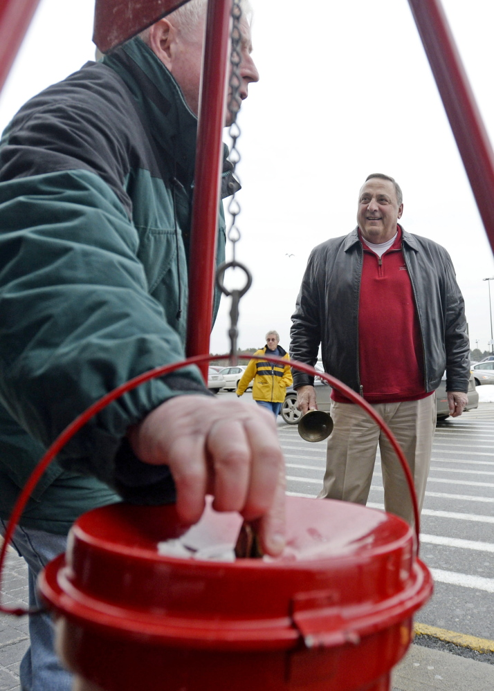 A shopper drops money into the Salvation Army kettle as Gov. Paul LePage rings the bell at Walmart in Biddeford on Friday.