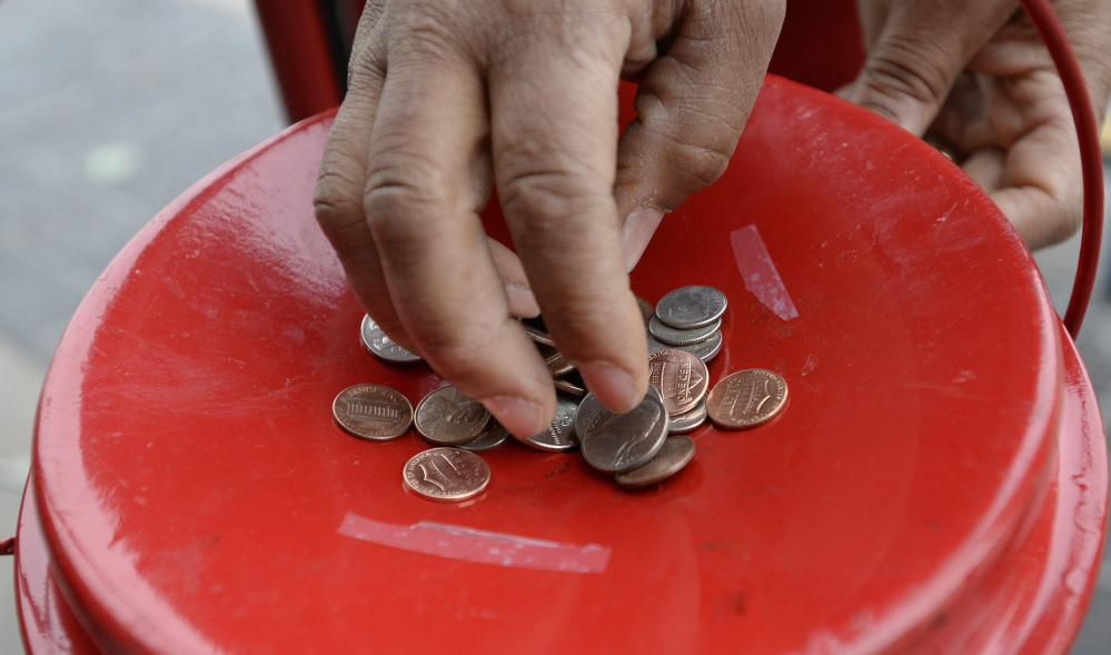 A Walmart shopper drops change into the Salvation Army Kettle in Biddeford on Friday.