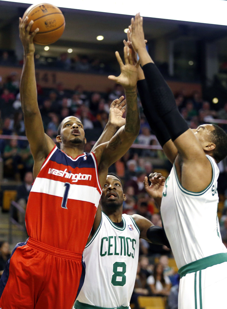 BIG GAME, BIG RALLY: Washington's Trevor Ariza, left, shoots against Boston's Jeff Green, center, and Jared Sullinger in the first quarter Saturday in Boston. Ariza scored 27 points and the Wizards beat the Celtics 106-99.