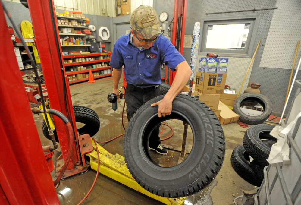 NOW TIRE SEASON: Leland Bradford, 18, places a snow tire on a stand to install metal studs at VIP in Waterville on Saturday to stay ahead of the demand this winter.