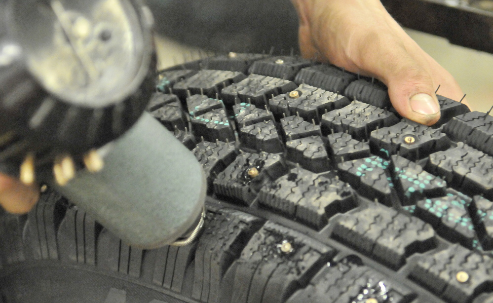 Preparations: Leland Bradford, 18, installs metal studs to snow tires at VIP in Waterville on Saturday to stay ahead of the demand this winter. VIP has seen an increase in studded snow tire sales as people gear up for Sunday's predicted ice storm.
