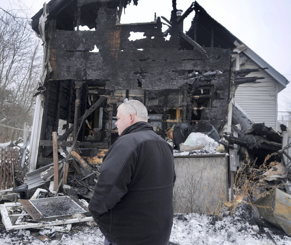 AFTERMATH: Investigator Ken MacMaster, of the Office of State Fire Marshal, inspects a Gardiner home Saturday that was damaged heavily by fire the night before. Investigators and Farmingdale firefighters were attempting to determine a cause of the blaze.