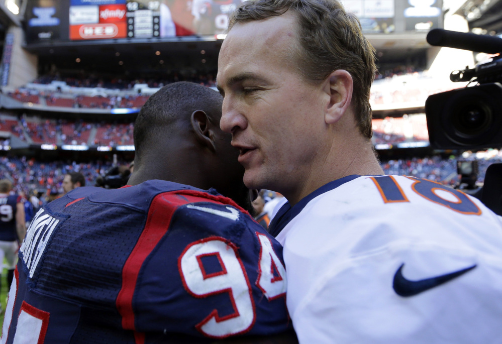 Denver Broncos' Peyton Manning, right, hugs Houston Texans' Antonio Smith (94) following an NFL football game, Sunday, Dec. 22, 2013, in Houston. Manning threw his 51st touchdown pass of the season to set a new NFL record.