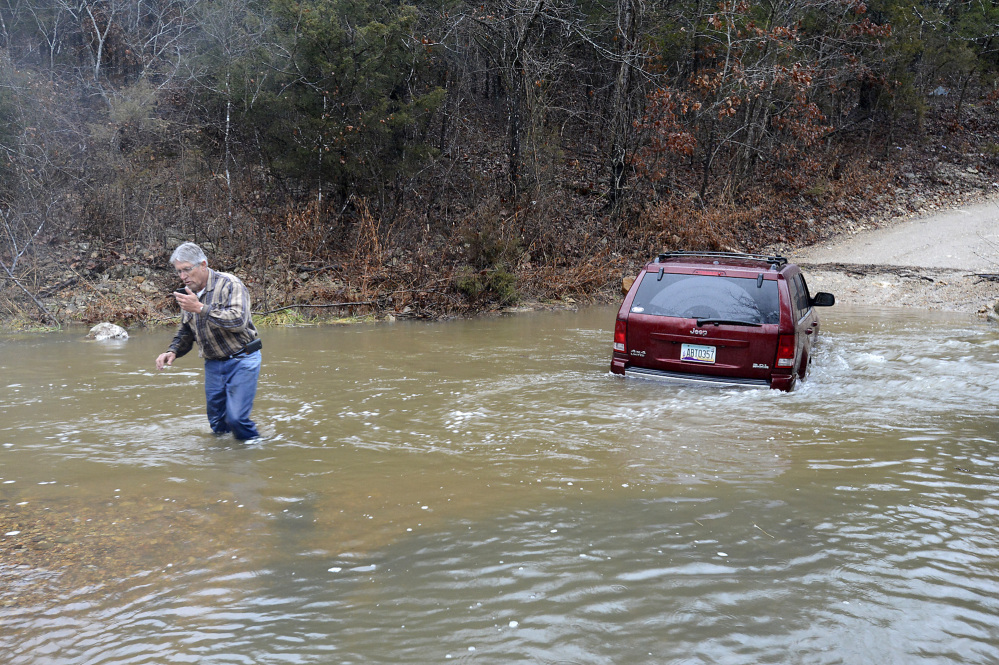 David Puffer calls for help after he stranded his vehicle in floodwaters on Saturday, Dec. 21, 2013 in Baxter County, Ark. The National Weather Service has issued a tornado watch in southeastern Arkansas and flood warnings and watches in much of the remainder of the state.