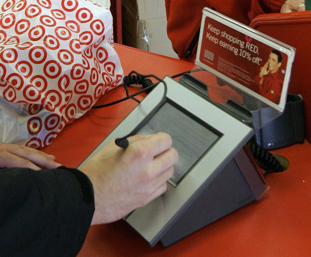 A customer signs his credit card receipt at a Target store. U.S. credit and debit cards are easier to copy, experts say, because of the magnetic strip they use instead of digital chips.