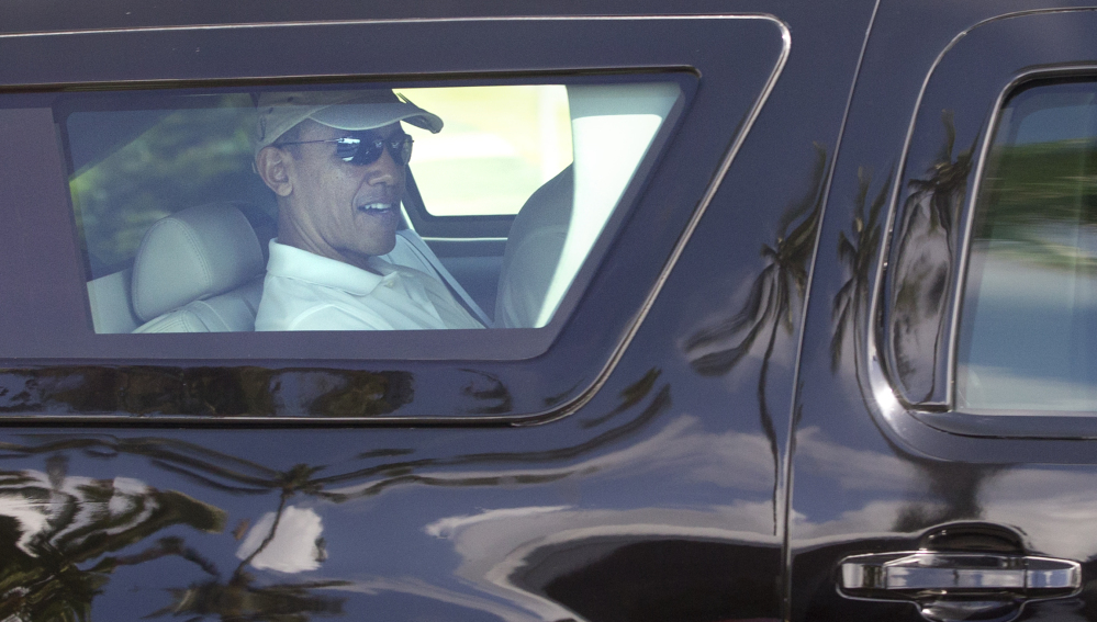 Palm trees are reflected in President Barack Obama's motorcade vehicle as he is driven through the Kailua, Hawaii, neighborhood where he is spending his annual holiday vacation with his family, Saturday, Dec. 21, 2013, en route to Marine Corps Base Hawaii in Kaneohe, Hawaii, to play golf.