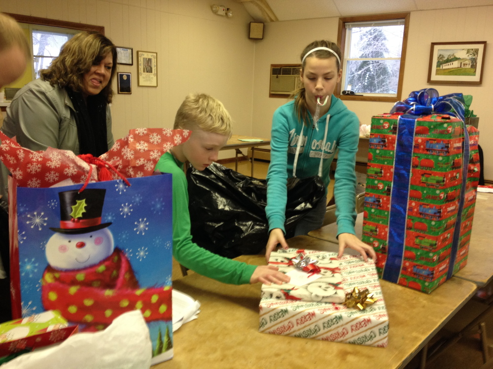 Christmas spirit: Ryan Gray, 8, left, and Olivia Bourque, 12, help distribute donated gifts to Maine Department of Health and Human Services caseworkers Monday morning at Sacred Heart Parish Hall in Hallowell. The presents, largely bought by parishioners of three Hallowell churches, will be given to families in need before Christmas.