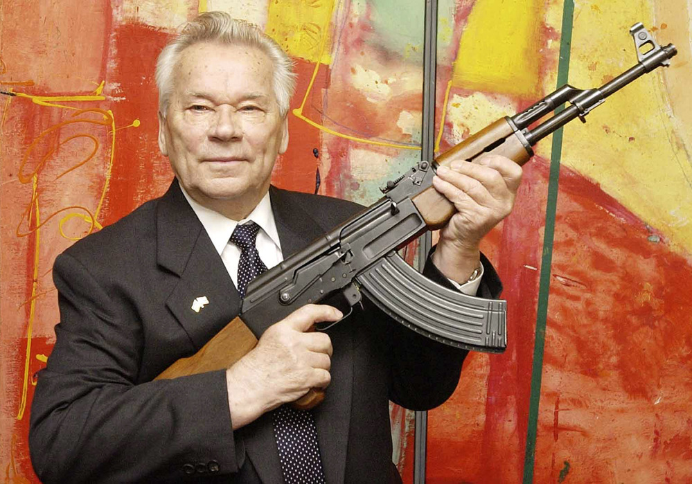 """Russian weapons designer Mikhail Kalashnikov presents his legendary assault rifle to the media while opening the exhibition """"Kalashnikov - legend and curse of a weapon"""" at a weapons museum in Suhl, Germany, in this 2002 photo."""