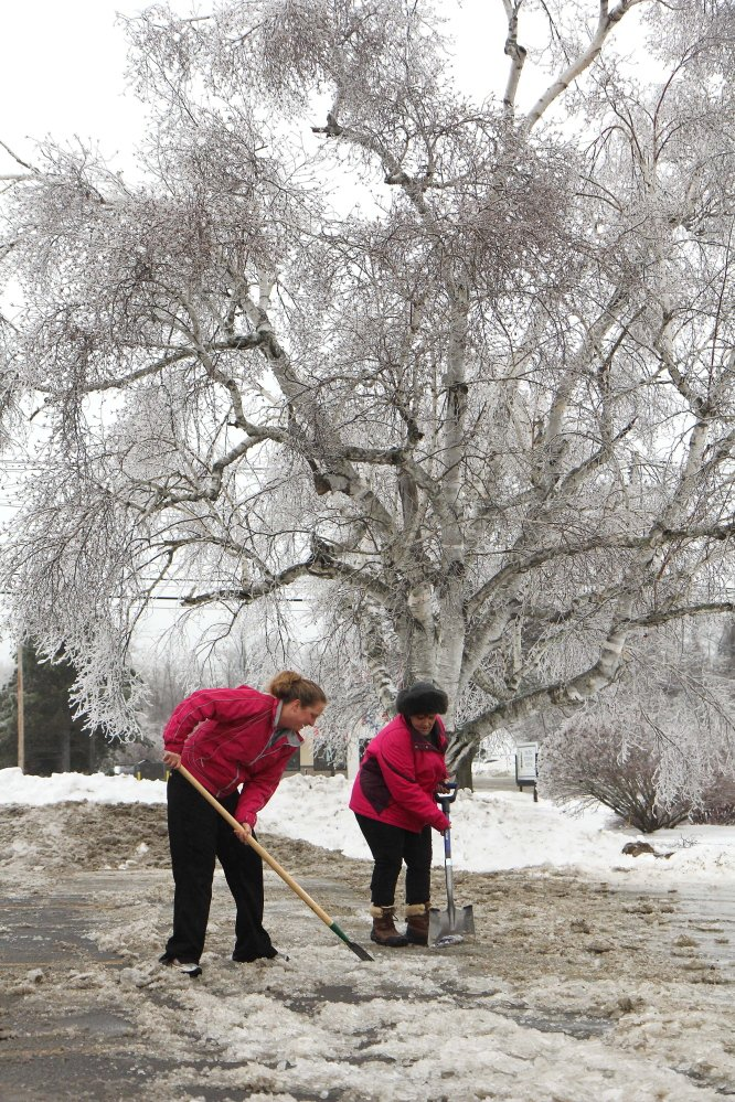 """Photo by Jeff Pouland ICE WORK: Pine Tree Veterinary Hospital employees Shannon Clements, left, and Denise Nadeau work to clear their parking lot of thick ice at the clinic located off Western Avenue in Augusta on Monday. """"I remember '98. I can live without that, """" said Nadeau. Though this ice storm wasn't as bad as the one in '98, it still caused a lot of headaches for residents of central Maine."""