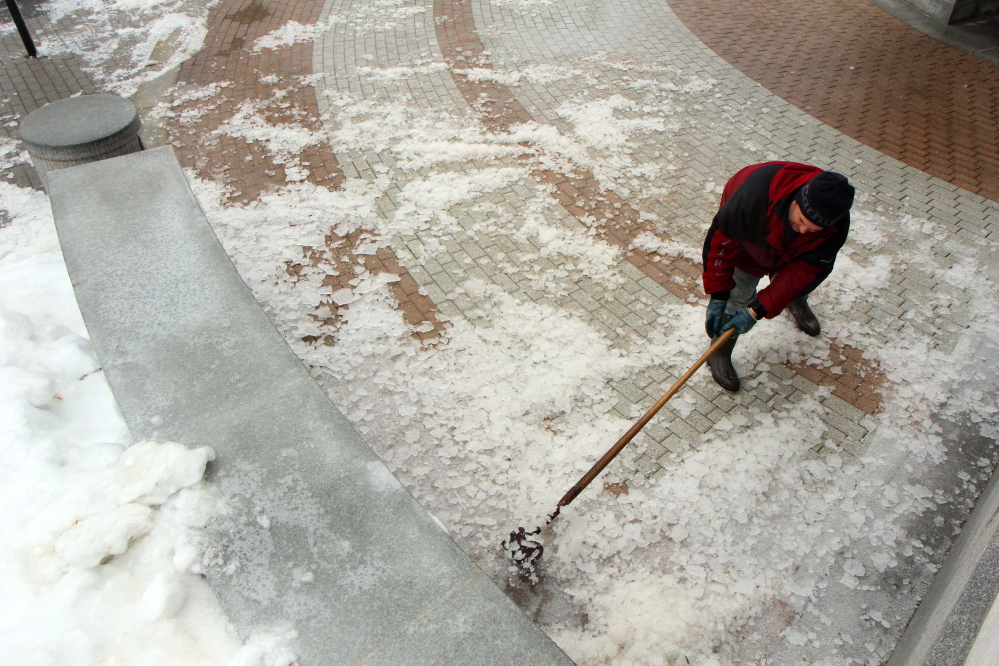 Photo by Jeff Pouland BREAKING IT UP: Clinton Coutts of the Bureau of General Services works to clear ice near an entrance to the State House in Augusta during Monday's storm.