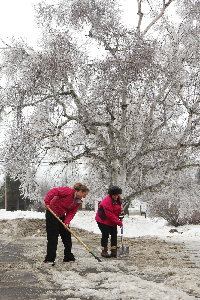 Photo by Jeff Pouland ICE WORK: Pine Tree Veterinary Hospital employees Shannon Clements, left, and Denise Nadeau work to clear their parking lot of thick ice at the clinic located off Western Avenue in Augusta on Monday.