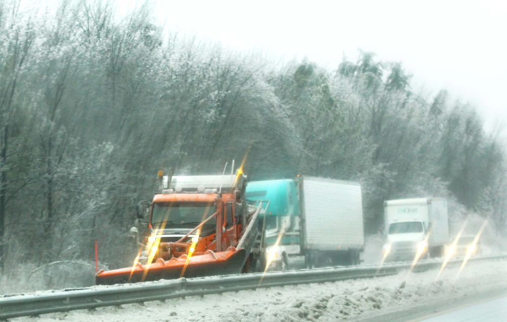 Photo by Jeff Pouland CLEARING THE WAY: A plow truck works to clear the northbound lane of Interstate 95 in Augusta during Monday's storm.