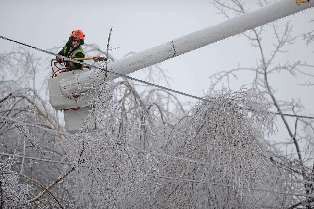 LINE CLEARING: Andrew Powers, an arborist with Asplundh Tree Experts, clears power lines from iced branches along Mayflower Heights Drive in Oakland on Monday.