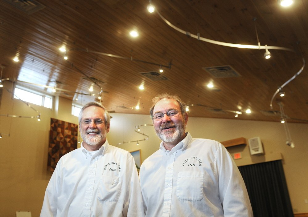 "CHAMBER AWARD: Scott Cowger, left, and Vince Hannan stand beneath mercury-free LED lights they installed in the ""Gathering Place"" room at their eco-friendly Hallowell inn, Maple Hill Farm. The couple are being recognized by the Chamber of Commerce with the President's Award."