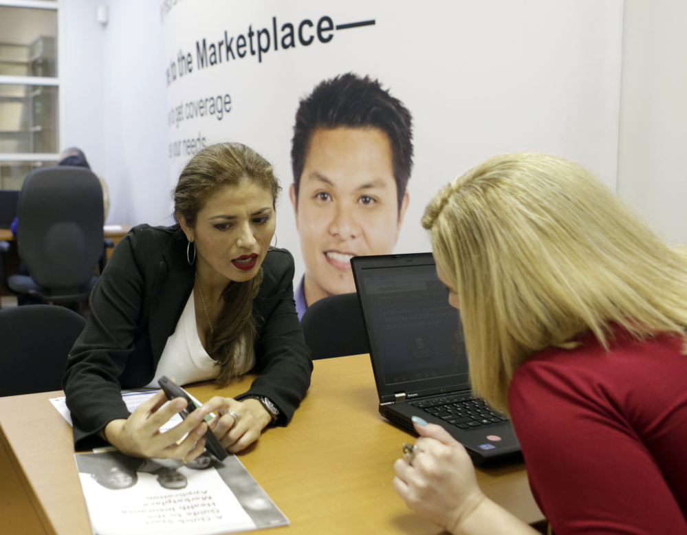 Johanna Diaz, left, points out information to Senior Certified Enrollment Specialist Marlene Nesmith at a Healthcare Marketplace office in Miami.