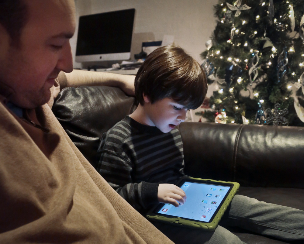 Adam Cohen looks as his son Marc, 5, uses a tablet at home in New York. Adam Cohen, a stay-at-home father of two, says apps have been a key part of Marc's education since he was just a baby.