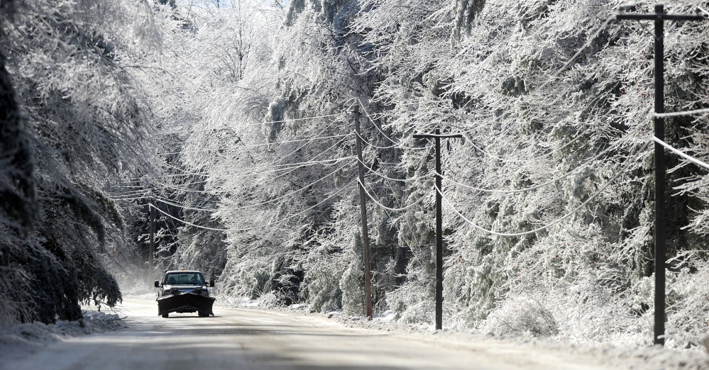 POWER OUTAGE: Sunlight emerges from the clouds on an icy West Road in Belgrade on Tuesday after an ice storm hit the area in recent days. Central Maine Power Company reported that most of its roughly 2,500 customers in Belgrade were without power and that about 38,000 customers were without power in Kennebec County about noon.