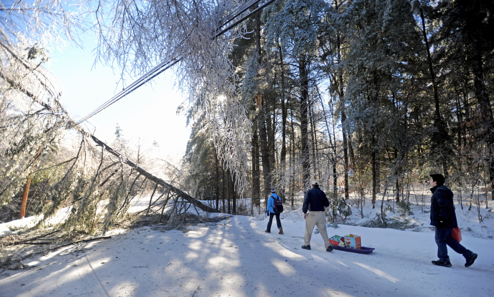 Staff photo by Michael G. Seamans STORM RECOVERY: Chris Devine, center, hauls a sled of gifts with his daughter Jordan, 11, left, and step-son Derek Gervais, 20, right, to their home on Maplehurst Lane in Belgrade on Wednesday, Dec. 25, 2013. The Devine's lost power on Monday and haul their supplies in on sled. Trees and power line are down on both sides of their driveway, luckily they weren't home when the trees fell affording them the opportunity to drive to town for gas and other essentials for life off the grid.