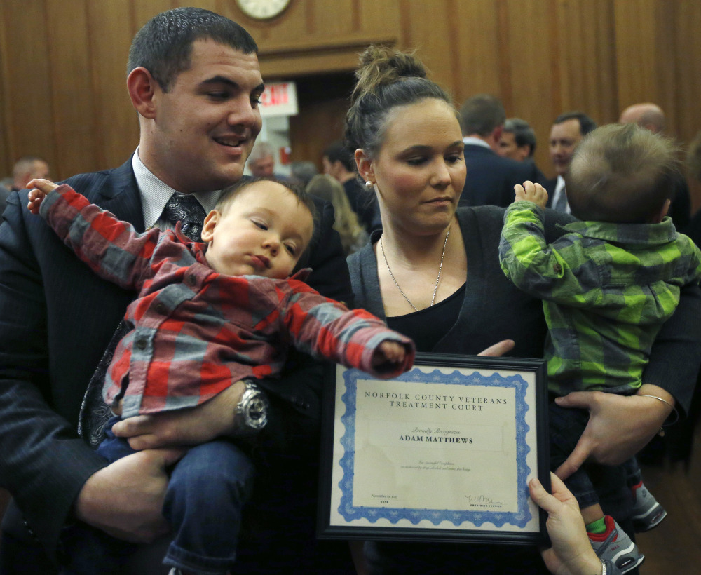 Adam Matthews, 23, of Bellingham, Mass., holds 10-month-old Jacob while his wife, Alexa, holds twin brother Jackson as they receive a certificate from the Norfolk County Veterans Treatment Court in Dedham, Mass.