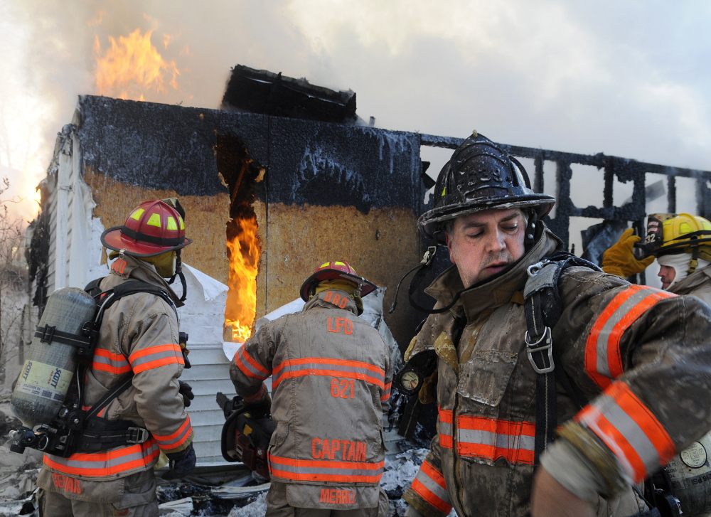 Staff photo by Andy Molloy FLAMES: Firefighters take cover from smoke and flames Wednesday while battling a fire on the Plains Road in Litchfield. Dozens of volunteer firefighters from area communities responded to the blaze that injured one man, destroyed a garage and heavily damaged the attached home.