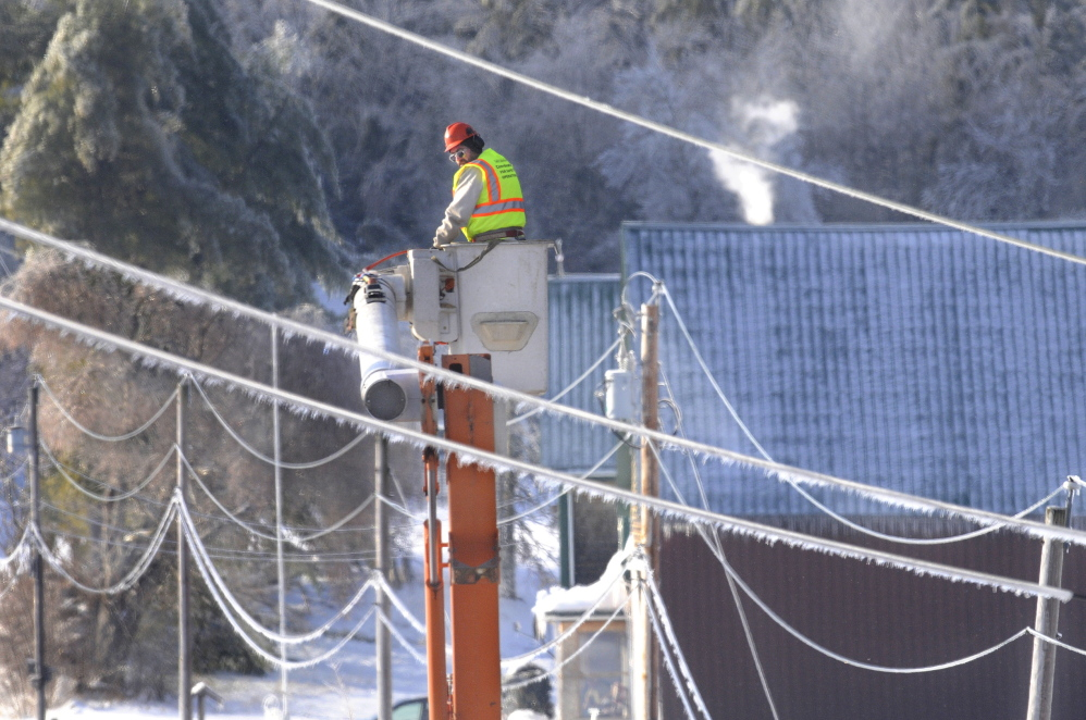 "Staff photo by Andy Molloy ICE OUT: Asplundh Tree Expert Co arborist Randy Patten descends between frozen power lines Wednesday in Farmingdale after clearing limbs away from utility poles. Several hundred out of state utility and tree workers arrived in Kennebec County on Christmas to restore power. Patten travelled from Vermont with fellow arborist Ray Coutu to remove fallen branches overhanging hazardous power lines. """"You do what you got to do to help people,"" Patten said. ""Particularly on Christmas."""